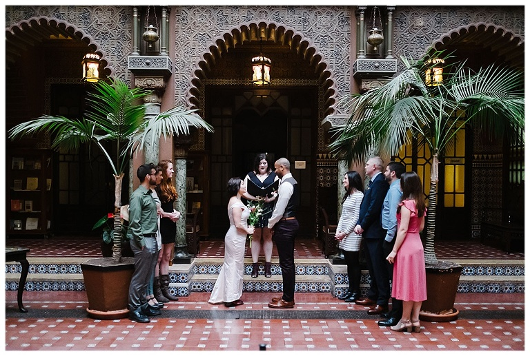 urban elopement ceremony with small number of guest in Lisbon, couple at the middle in front of ornamented door